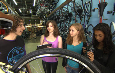 SciGirls in bike shop talking to store employee about bikes
