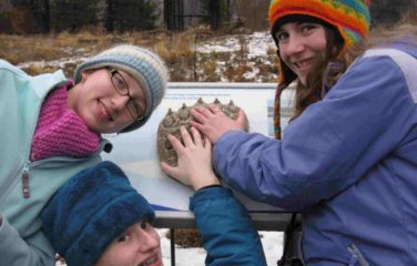 Three SciGirls touching a polar bear paw mold